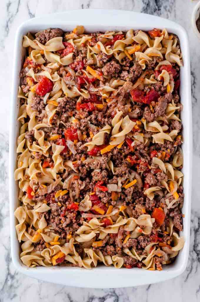 Cheesy beef and noodle casserole in a baking dish ready for the oven.