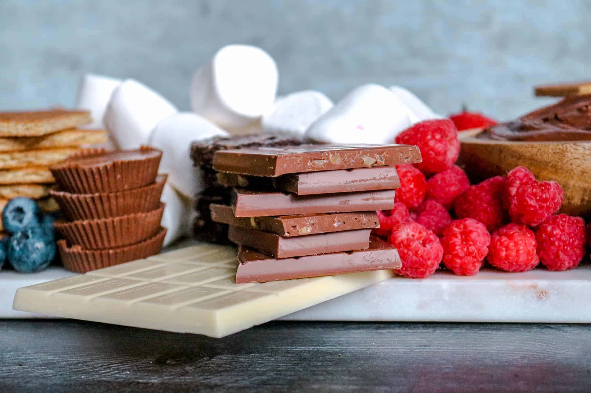 How to Make a Loaded S'mores Board: head on shot of chocolate bars, peanut butter cups, raspberries, blueberries and marshamllows