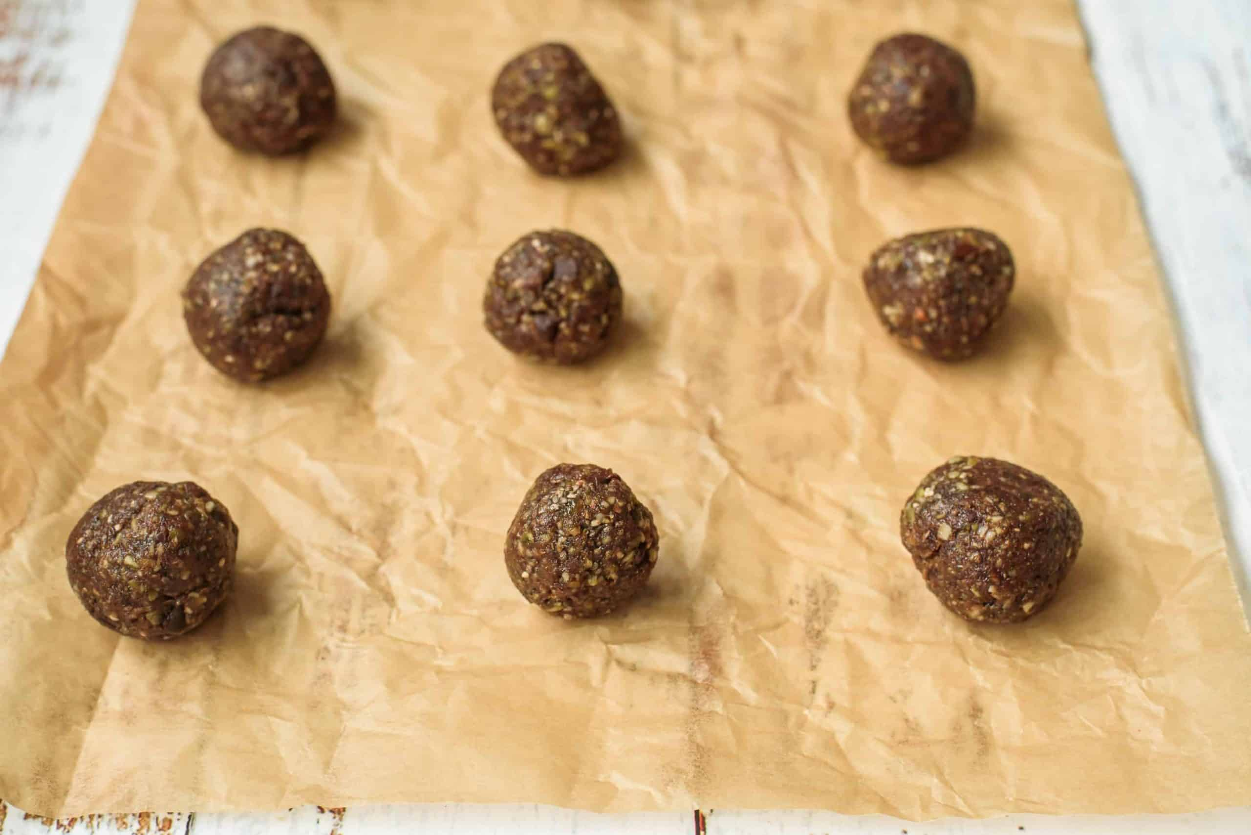 Closeup of Peanut Butter Crunch Balls on Parchment lined Baking pan.