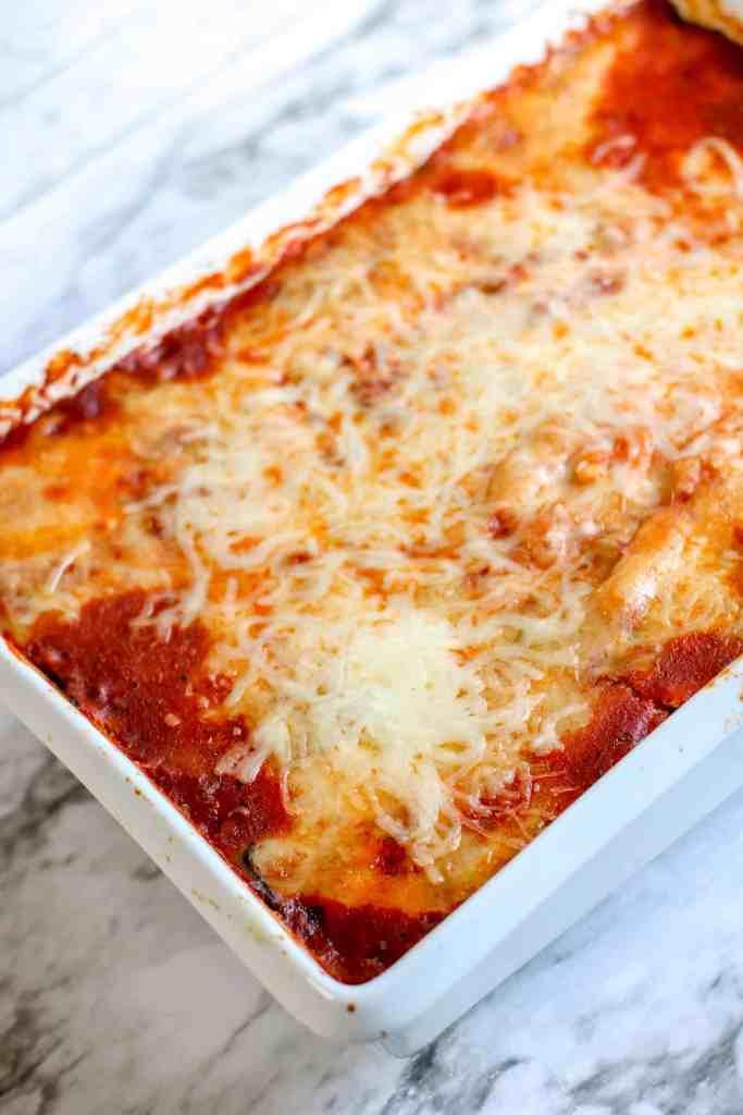 Full pan of cheesy lasagna in a white ceramic baking dish.