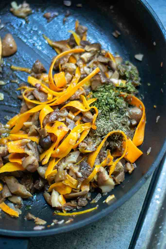Carrots and mushrooms and herbs in a sauté pan.