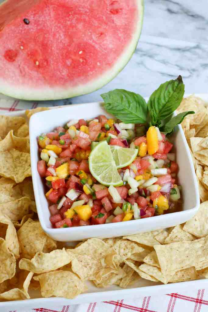 Watermelon salsa with lime slices on top and mint on the side, surrounded by tortilla chips with watermelon above it on a marble background.