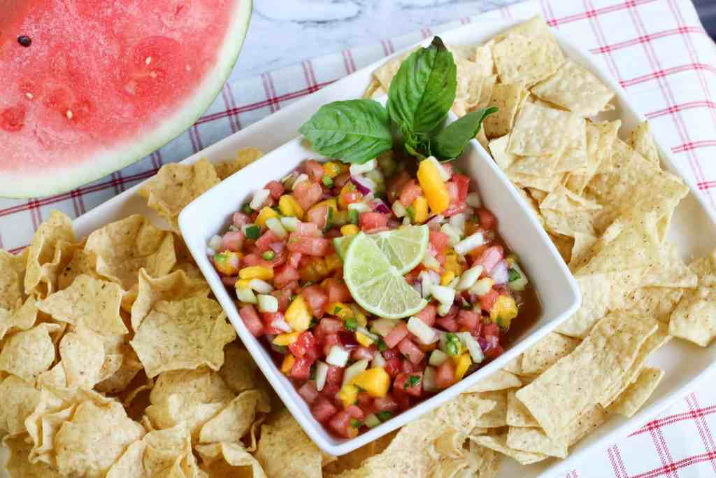 Watermelon salsa in a white square dish with chips around it and a slice of watermelon on the side.