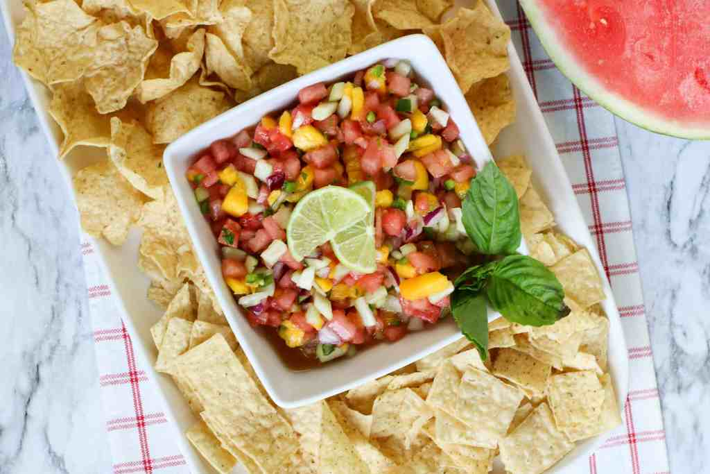 Fresh watermelon salsa topped with lime slices and mint surrounded by tortilla chip scoops.
