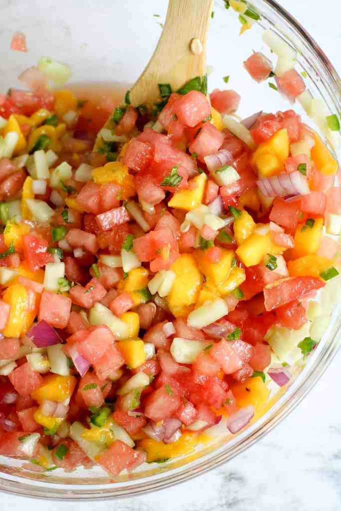 Fresh watermelon salsa being stirred with a wooden spoon in a large glass bowl.