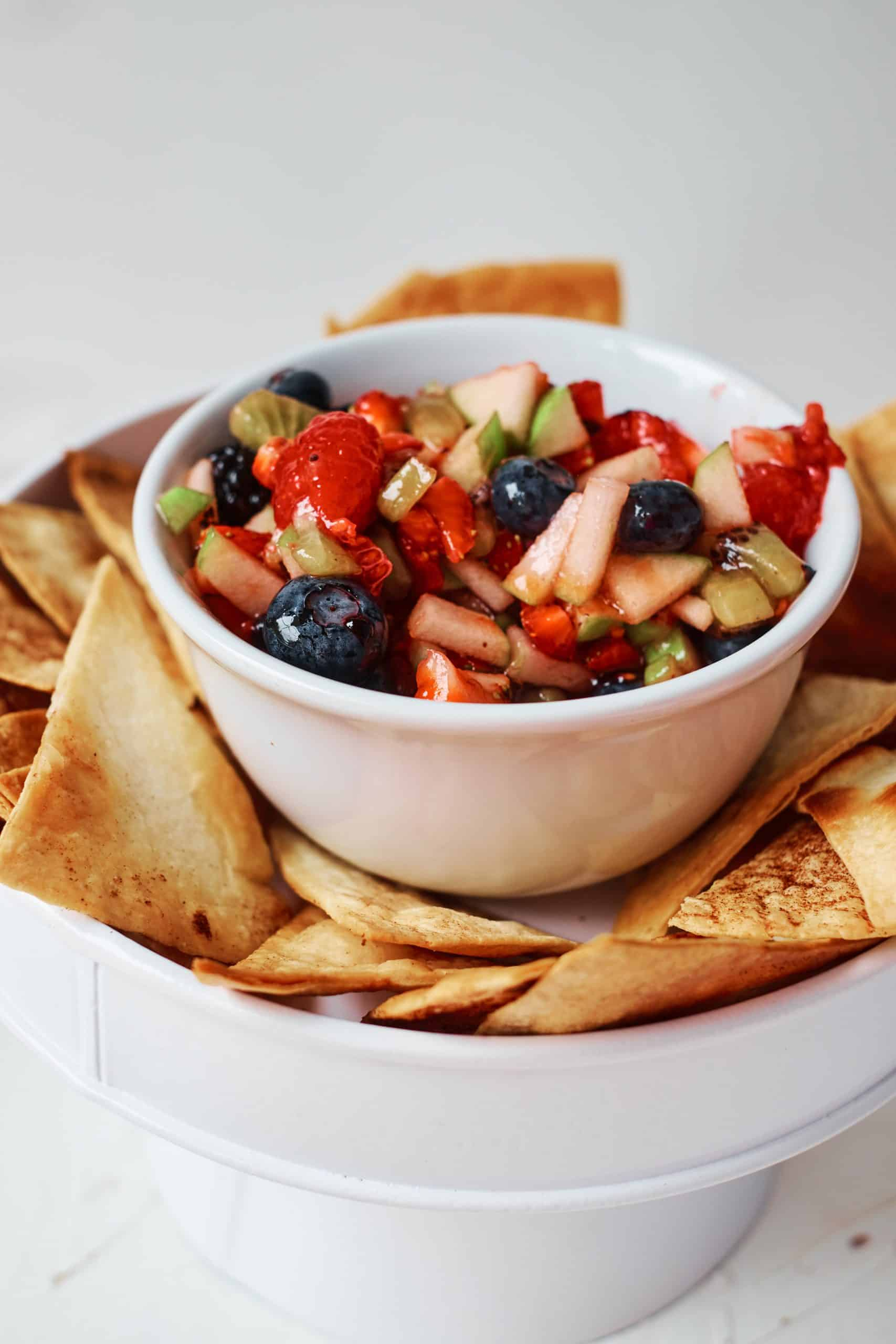 Fruit Salsa in a white bowl surrounded by homemade cinnamon tortilla chips.