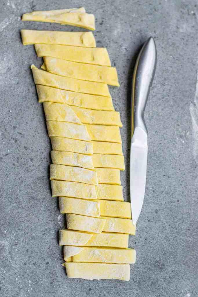 Cutting pasta dough into strips.