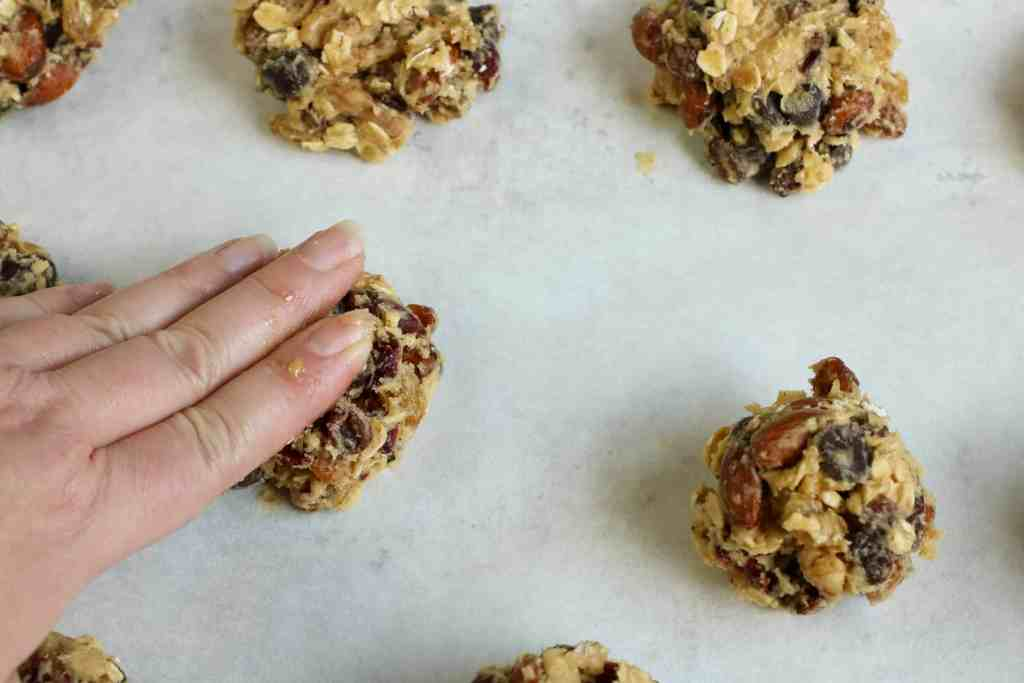Hand pressing down cookie dough on a pan lined with parchment paper.