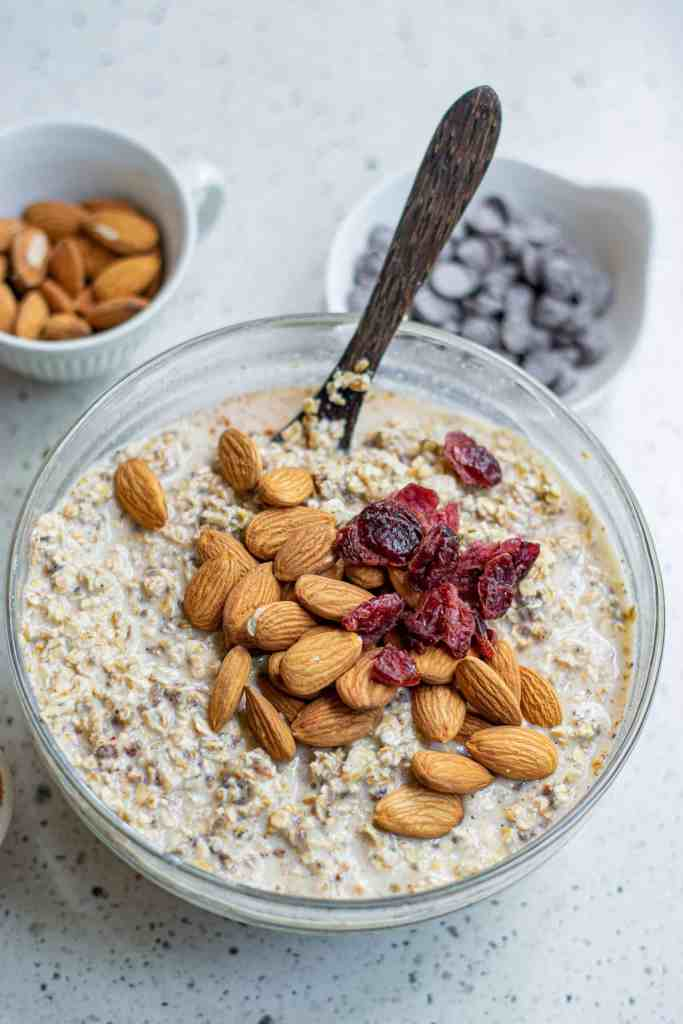 Almonds and dried cranberries on top of oats in a large glass mixing bowl.