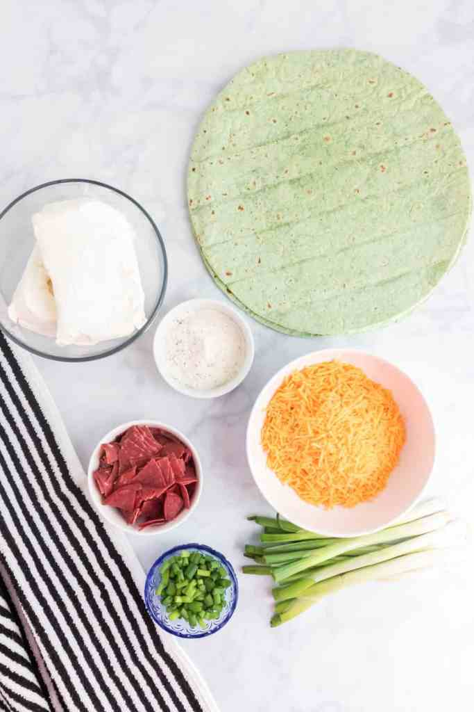 \Spinach Tortillas, cheddar cheese, dried beef, cream cheese and green onions on a white counter top
