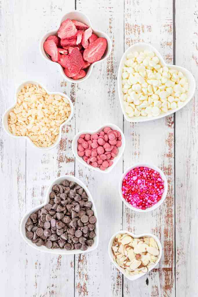 White chocolate chips and milk chocolate chips in white heart bowls. Freeze dried strawberries, pink melting discs, sliced almonds and Valentine's Day sprinkles in white bowls on a white wood background.