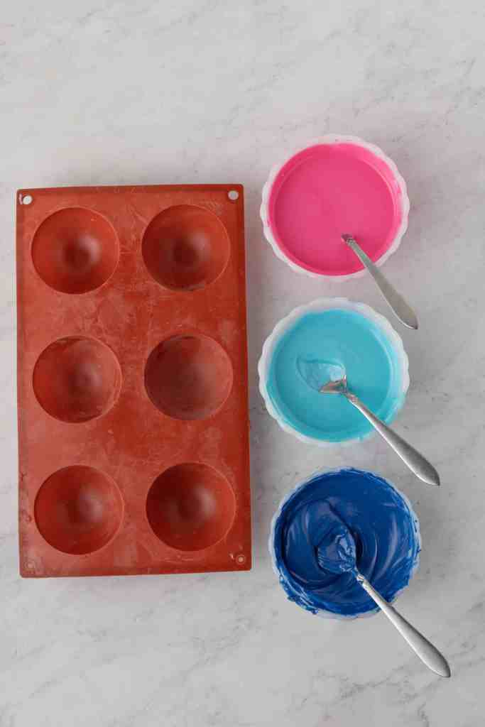 Pink, blue and purple candy melts in white bowls with spoons in them beside a silicone mold.