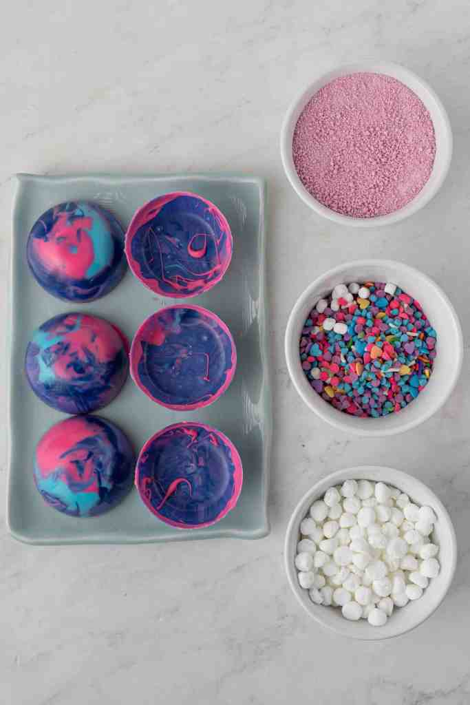 Galaxy half spheres on tray with ingredients to add into them in 3 bowls beside the.