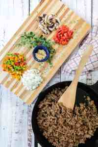 Browned meat in a black iron skillet beside a wooden cutting board with diced vegetables and herbs.