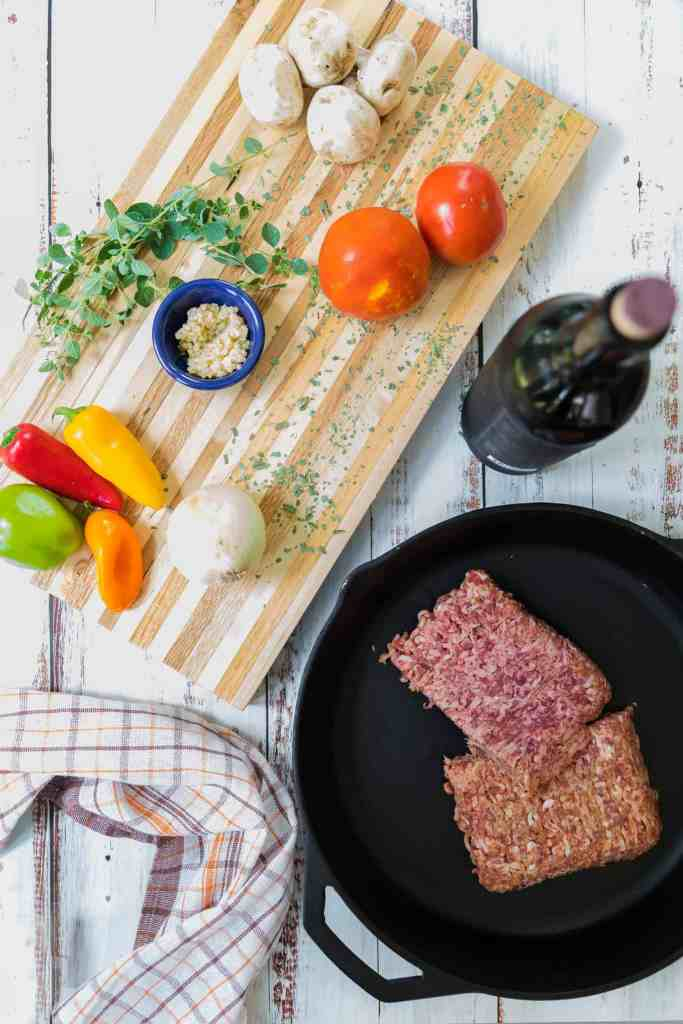Overhead view of ground meat in a black iron skillet, red wine and vegetables and herbs on a wooden cutting board.