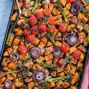 Overhead view of sheet pan chicken with vegetables.