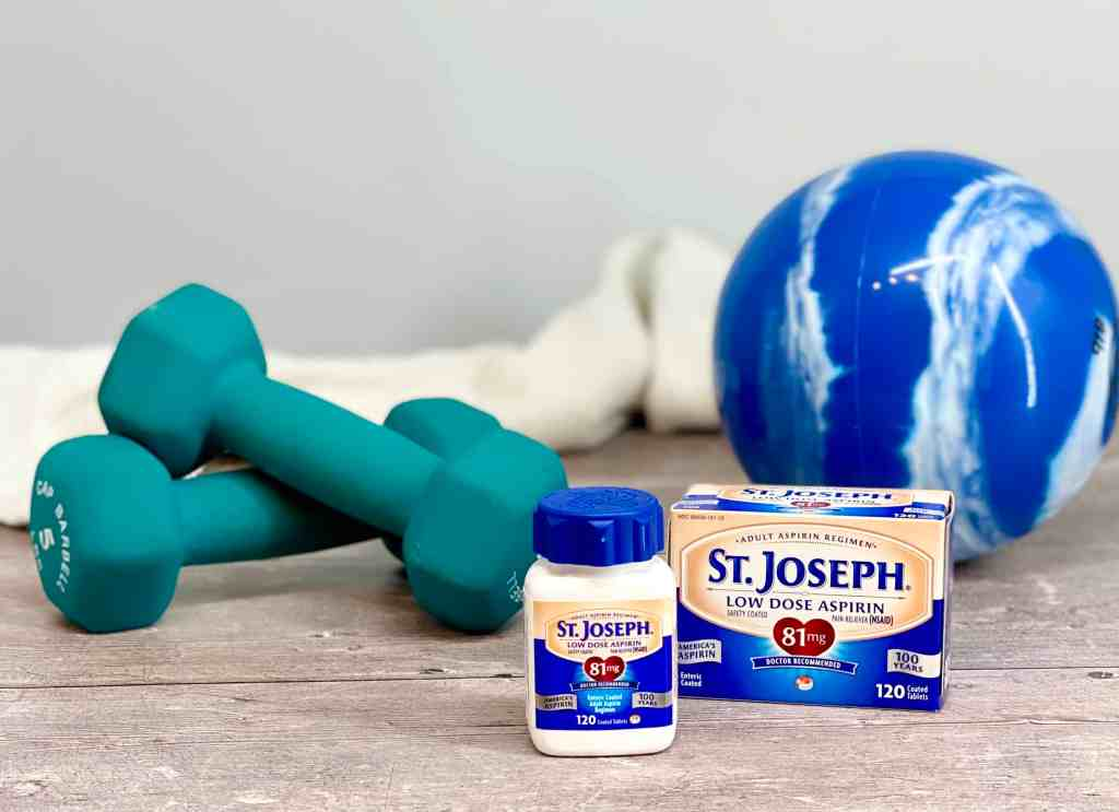 St. Josheph's Aspirinon a wood floor with weights and a medicine ball in the background.