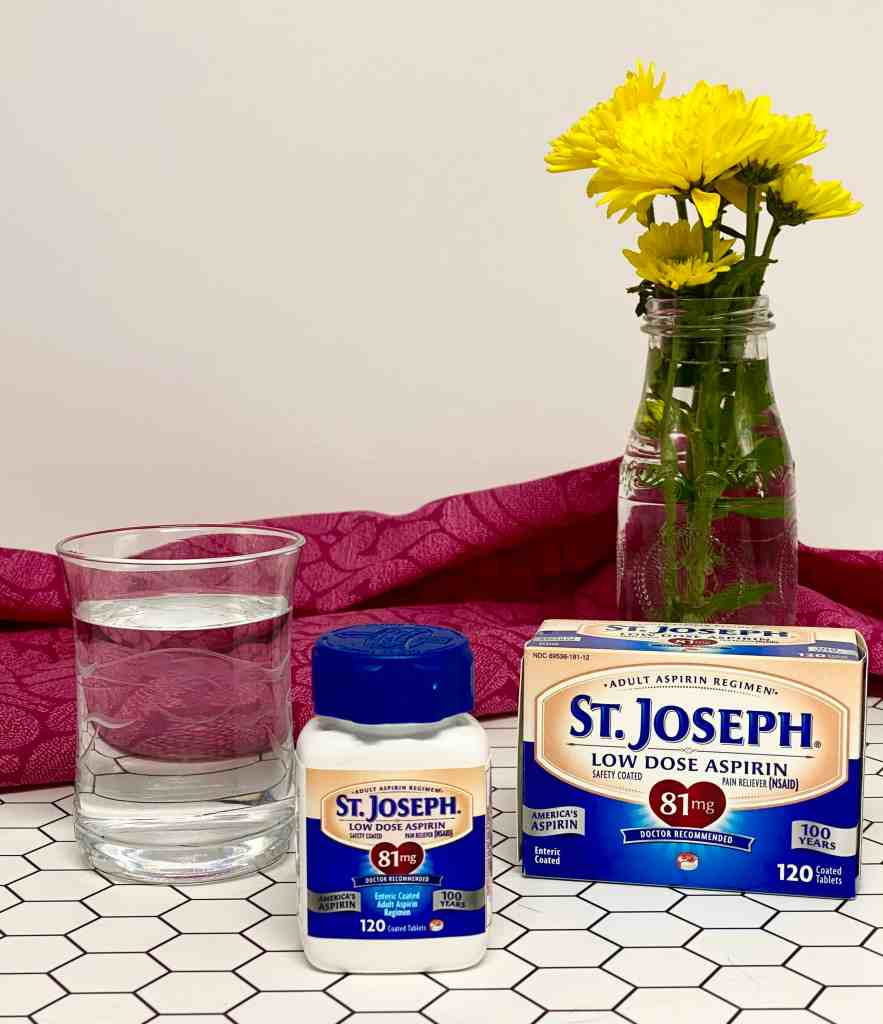 St. Joseph's Aspirin on a bathroom counter top with a glass of water and a vase of yellow flowers in the background.