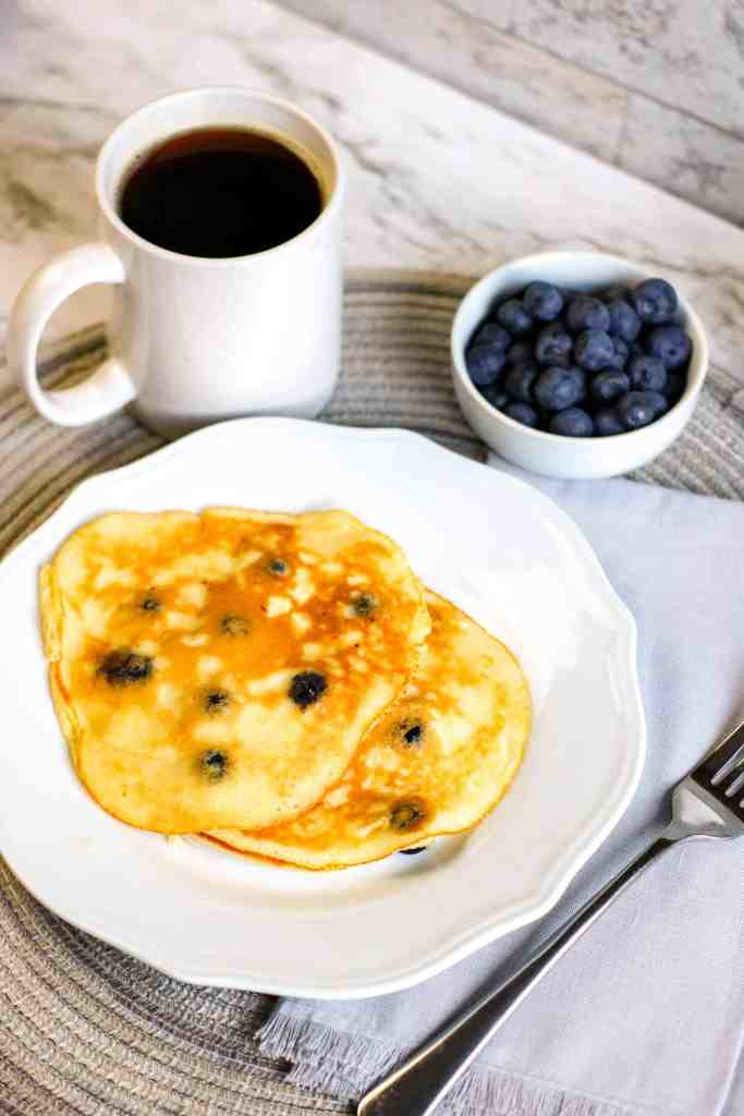 3/4 angle view of pancakes on a white plate with blueberries and coffee.