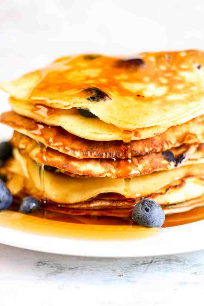 A stack of Keto Blueberry Pancakes with syrup dripping over the side.