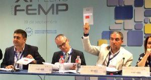 El presidente de la Diputación de Málaga, Elías Bendodo, con la mano alzada, este sábado en la asamblea de la FEMP. Foto/ Europa Press