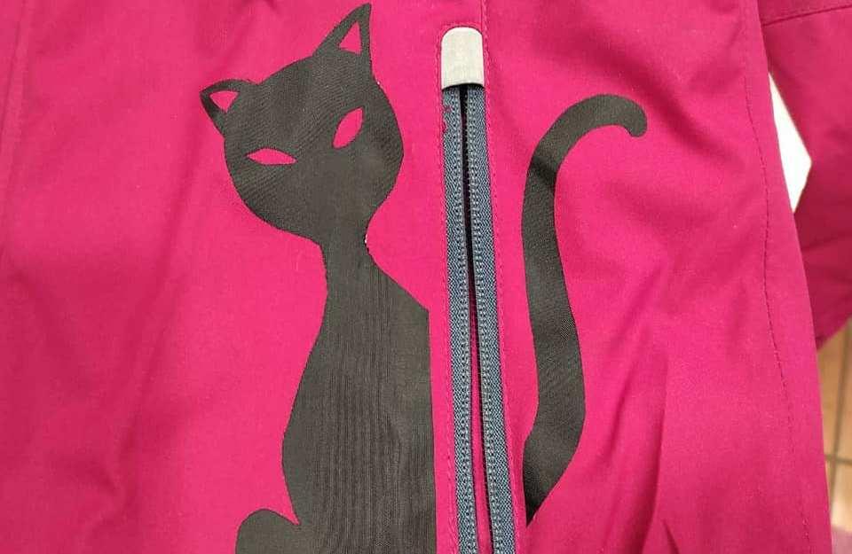Sagoma di gatto ritagliata nel copristrappi adesivo Marbet e applicata a giacca a vento strappata