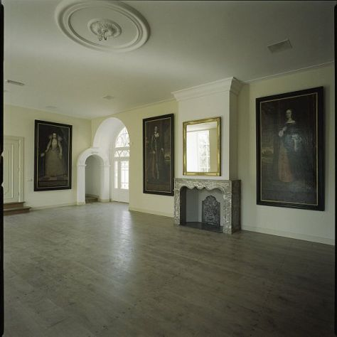 De gerestaureerde zaal met enkele portretten van de bewoners op de begane grond van het kasteel.