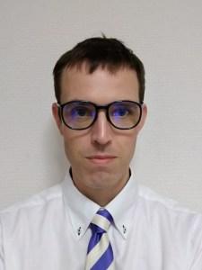 A portrait photograph of Marc Jones wearing glasses.