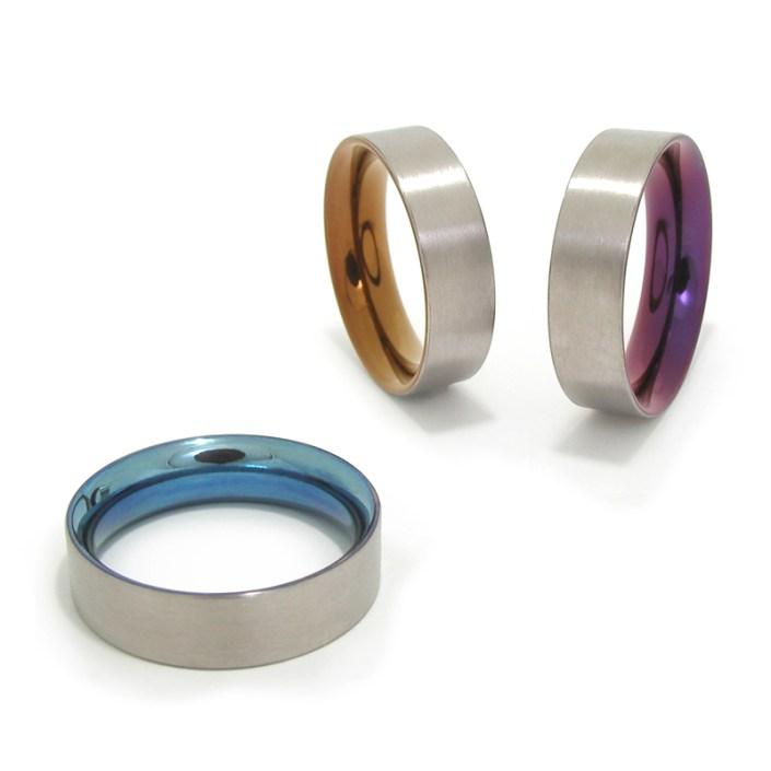 Titanium deels gekleurde ringen van Marc Lange 'Beauty Inside'. Aan de binnenzijde zijn de ringen gepolijst en gekleurd, aan de buitenkant zijn ze geschuurd afgewerkt en tonen ze de oorspronkelijke materiaalkleur.