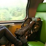 Female resting legs on a train seat with backpack