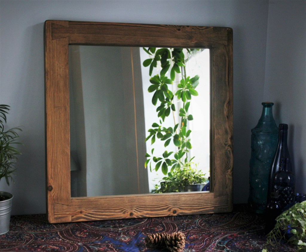 Our high quality wooden framed mirror comes in a dark stain and features our signature hand cut dovetail detailing at the mirror frame corners. This modern rustic wall mountable mirror has a wide wooden frame is handcrafted from a mixture of sustainable and reclaimed wood by Marc and our talented small team in our rural Somerset workshop, using traditional techniques. Update your home with our solid wooden furniture range, we can install near Somerset, Bath, Bristol, Dorset, Wiltshire and Devon.