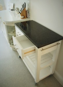 this custom handmade kitchen island, cart and trolley has been painted gloss white and features a solid granite worktop, chrome handles and towel rail. With 2 shelves and 2 drawers this premium kitchen unit has been designed  by Marc wood Joinery in Somerset UK and is available to buy from our online shop or we can visit locally if you are near Bath, Bristol, Exeter, Taunton or Sherbourne.