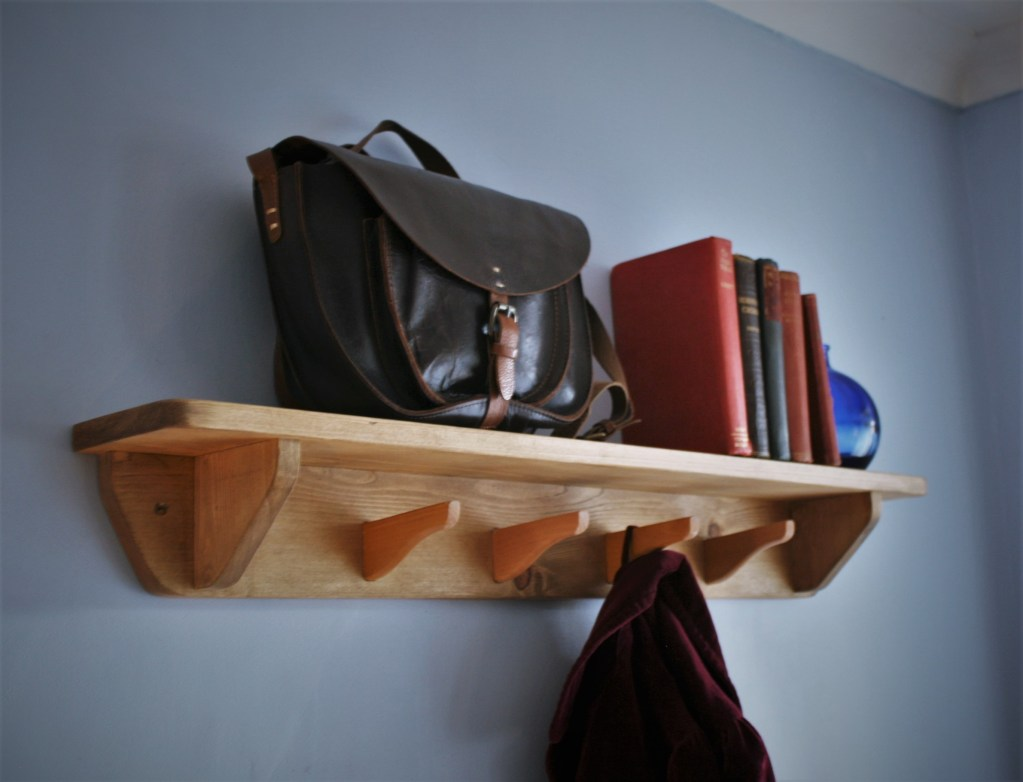 Our modern rustic custom handmade bedroom and hallway porch wall shelf with 4 upcycled coat hanger hooks measures 12 cm height X 90 cm width and 13 cm depth. This modern rustic architectural style wall shelf is deep enough for hats, books and ornaments and the 4 hooks are perfect for your bags, scarves and clothes. Our handmade country farmhouse wooden wall shelves and clothes storage pieces are each handmade by Marc Wood Joinery in Somerset UK from natural eco sustainable and reclaimed wood. They can be custom made to any size and we can arrange delivery or installation near Taunton Somerset, Sherborne Dorset, Exeter Devon, Bath or Bristol.