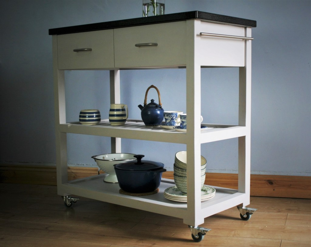 Our modern kitchen island on wheels is handmade from sustainable natural wood and with a chunky granite worktop, chrome handles and painted in a modern grey; contact Marc Wood Joinery in Somerset for custom made kitchen storage.