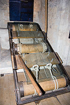 A rectangular metal frame with two wooden planks crossing its width.  Spaced equally along the frame are three large wooden rollers.  Attached to the rollers at each end are ropes, designed to act as restraints.  The entire contraption is covered with a sheet of clear plastic, upon which is sketched the outline of a man, his wrists and ankles 'through' the rope restraints.  The centre roller has a large wooden lever—turning this lever would pull the other two rollers in opposite directions.