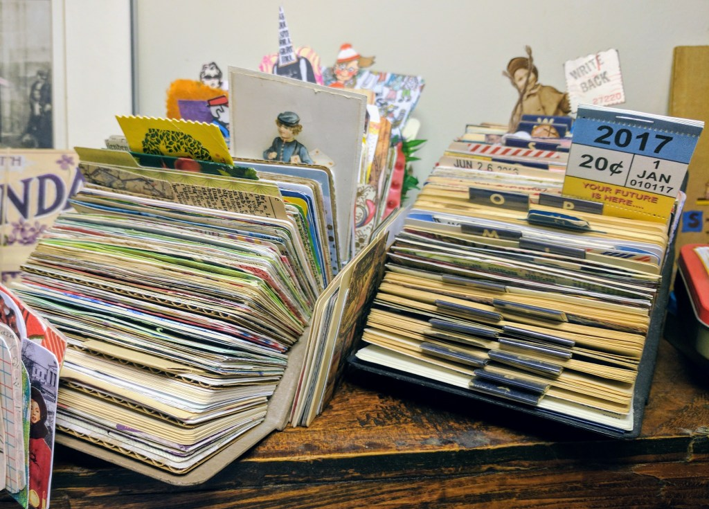 a display of collaged cards in a rolodex file