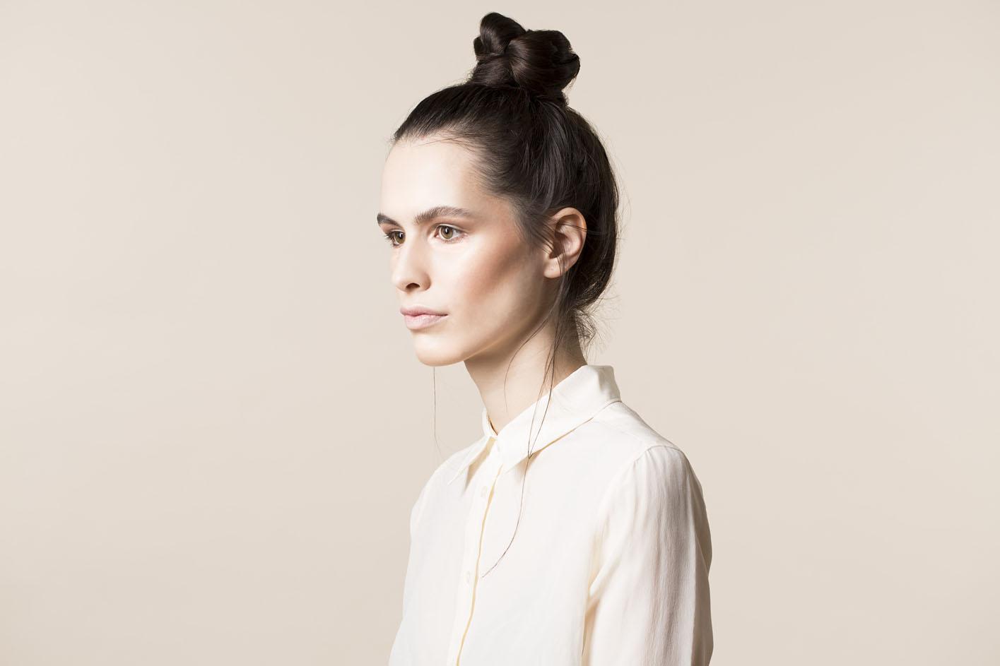 Photo: studio beauty cosmetics campaign photographer Margaret Yescombe, Make-Up Artist Hairstylist Dorota Nowacka, Model Elisabeth. Pale look, cream shirt, hair bun knot, profile portrait image