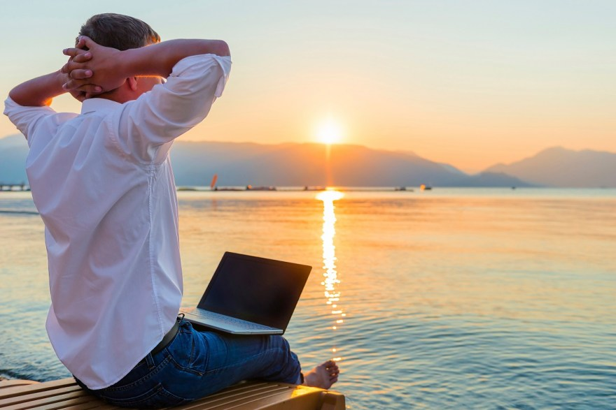 Recreational entrepreneur. Man with laptop in the morning on the beach working