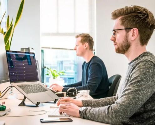 Imagem de duas pessoas trabalhando em computadores
