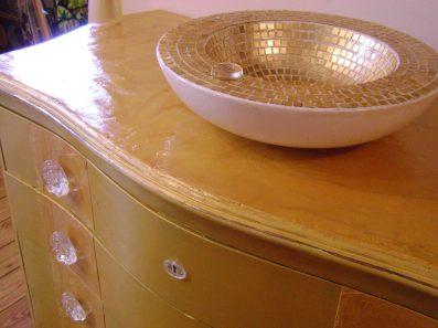 Resina sempre in oro pallido per il top del mobile. Maniglie e placche sono state riprodotte in resina trasparente