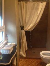 Una tenda in sostituzione del box doccia raccolta da un fermatenda in resina