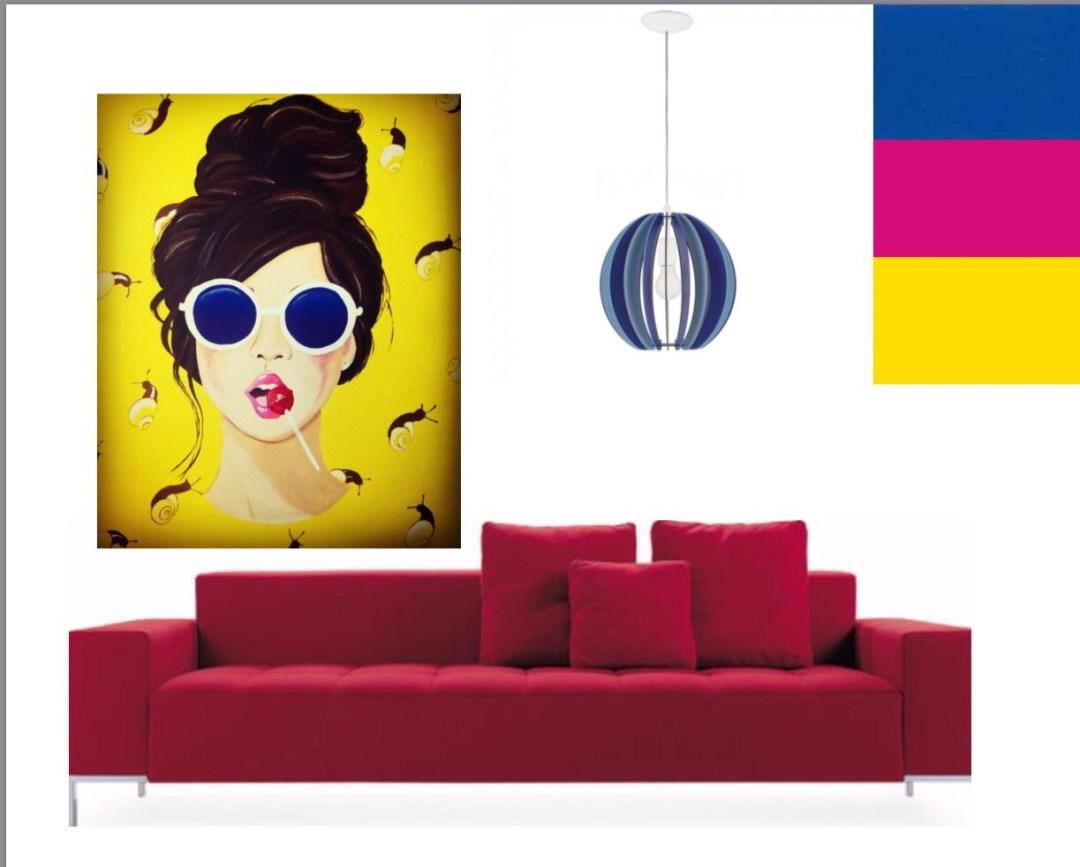 un divano grande su sfondo bianco color magenta, un quadro con donna mora capelli legati occhiali bianchi con lenti blu, una lecca lecca in bocca color magenta. Sullo sfondo giallo delle lumache gialle e nere, lampadario a sospensione blu e celeste con lampadina bianca