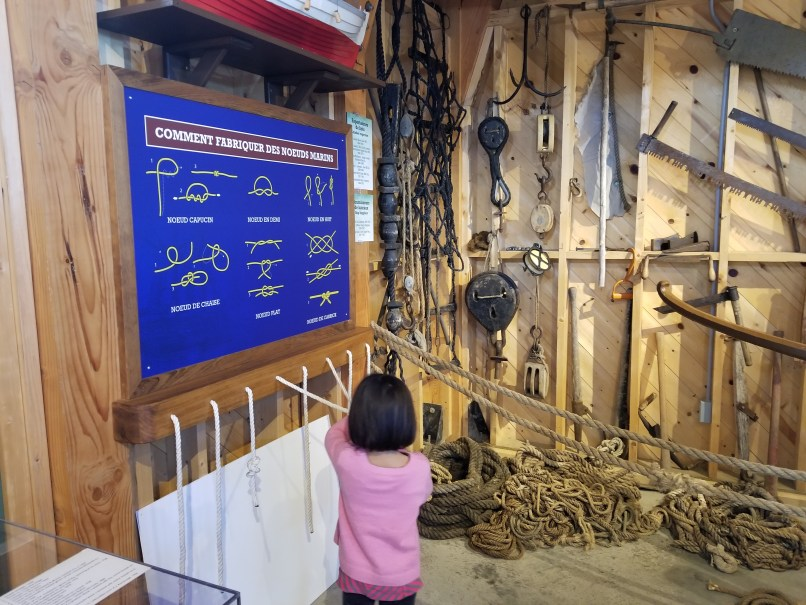 4-year-old girl learning to tie knots in Gaspe's histsoric village.