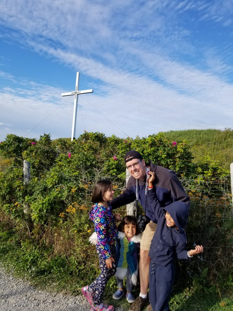Family in front of a cross in Perce, Quebec: a father with three children in front.