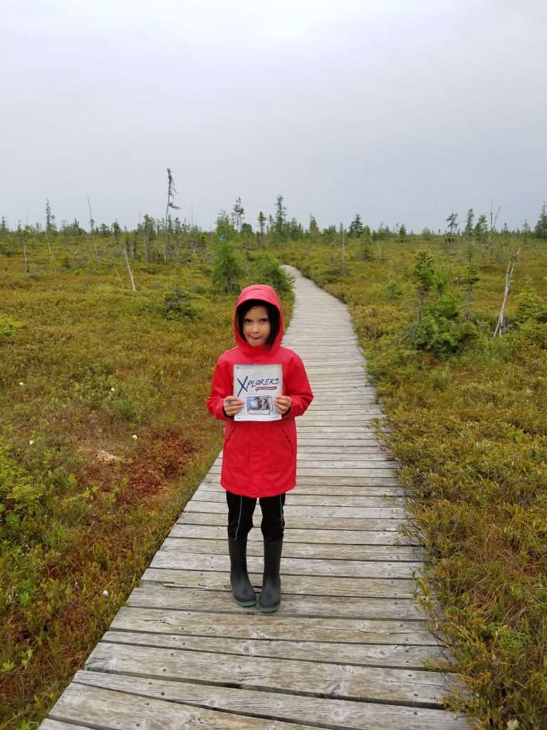 Girl in red raincoat holding an Xplorers National Park booklet. Kouchiboguac National Park, New Brunswick