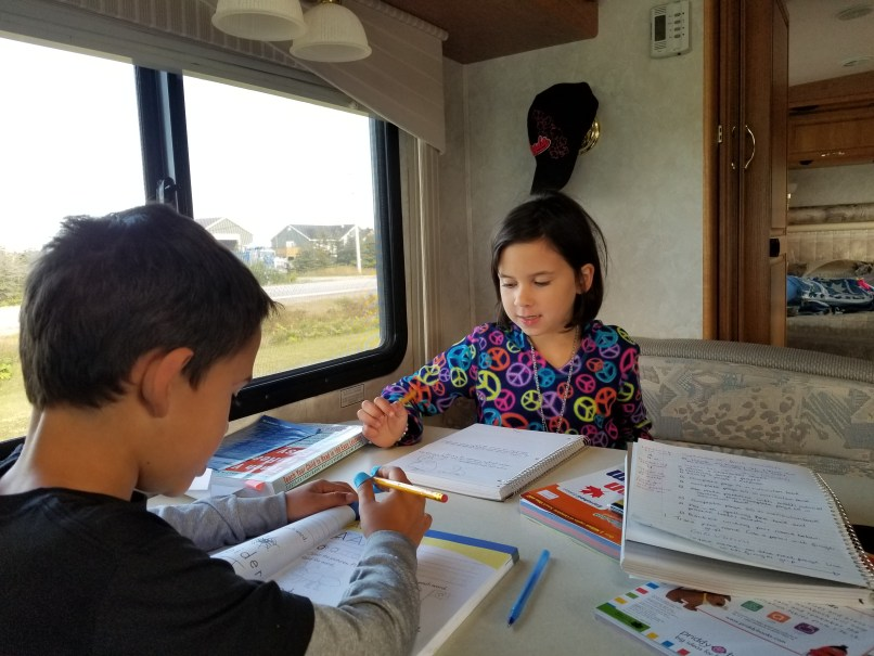 girl and boy completing homeschooling work inside an RV, the freedom of homeschooling, www.marianamcdougall.com