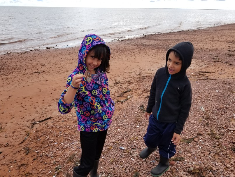 Girl holding a lobster claw and boy looking on at a beach in P.E.I, North Cape Coastal Drive.
