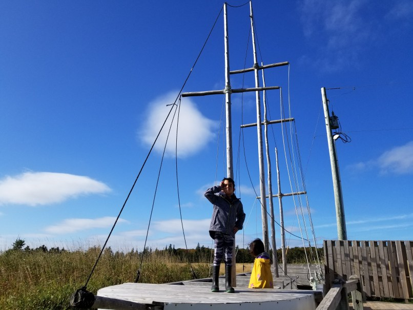 """Boy wearing a raincoat and standing on a """"pirate ship,"""" Basin Head Beach, PEI. A girl wearing a yellow raincoat stands in the background."""