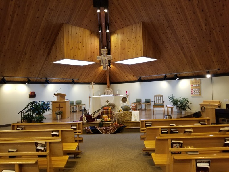 St. Francis of Assisi Catholic Church, Cornwall, PEI. The photo shows the altar and pews, as well as the crucifix that hangs from the ceiling. The altar has been decorated for Thanksgiving with pumpkins and gourds.