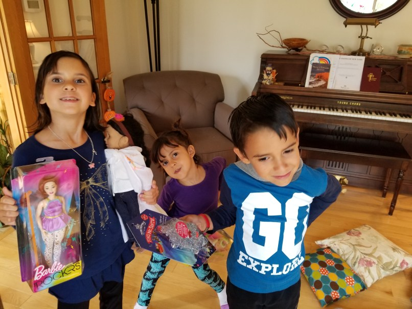 A girl, a girl, and a boy holding toys in a living room. A piano and chair are behind them.